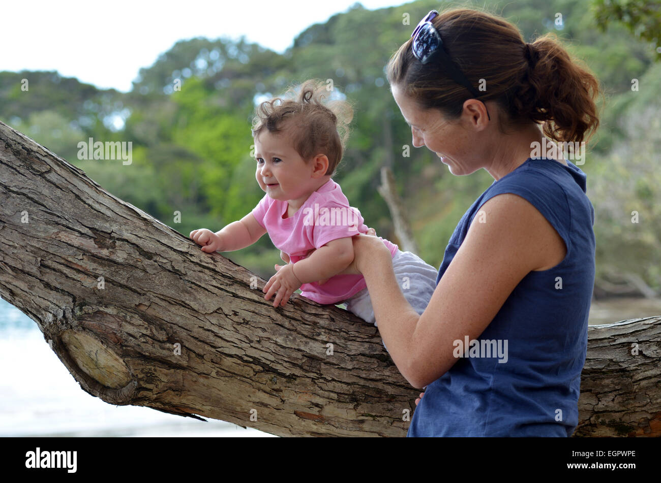 Young mother play outdoor with her baby (girl age 08 months). Concept photo of motherhood and mother and baby lifestyle - Stock Image