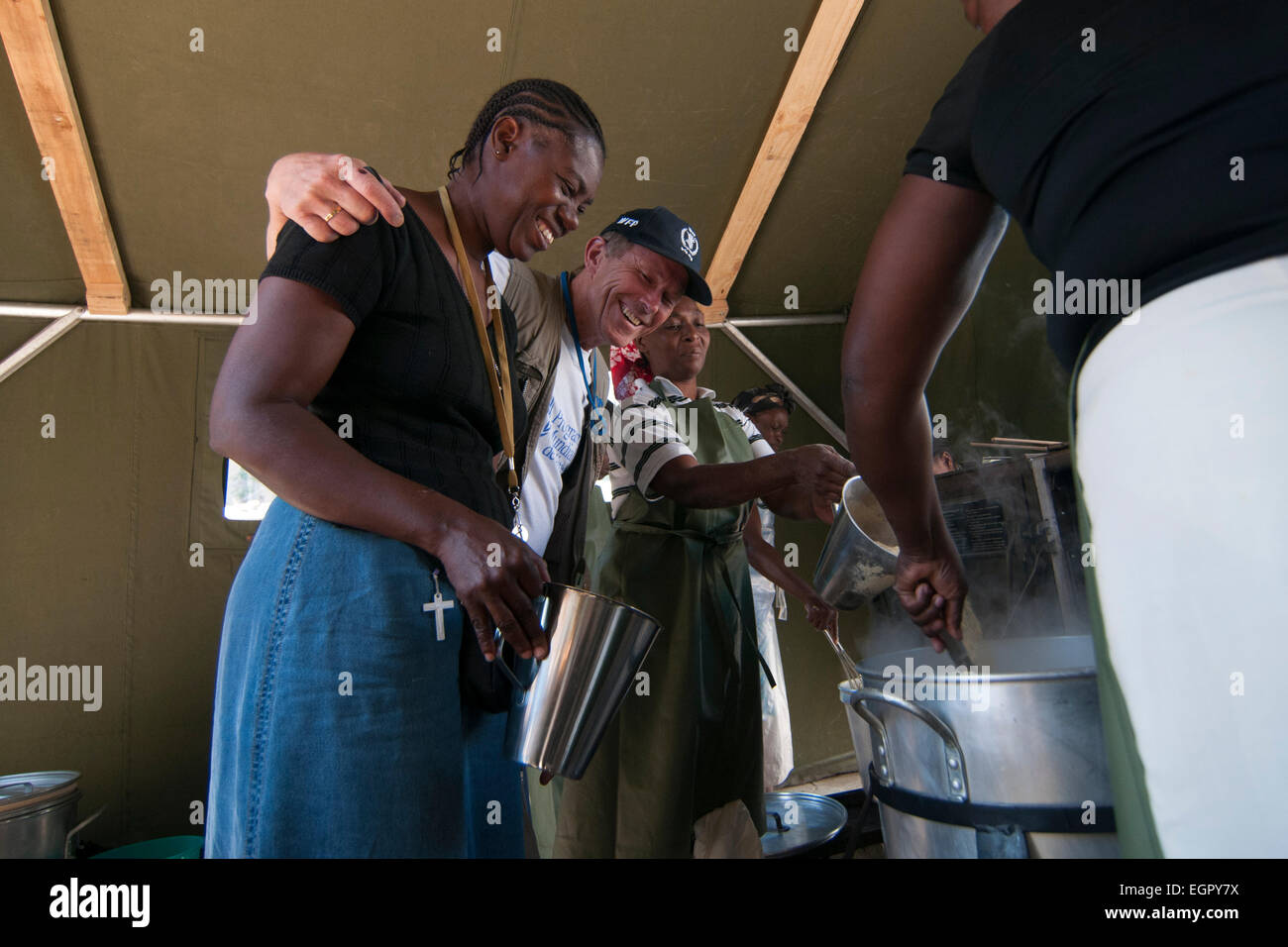 A WFP staff member with local women in a kitchen set up by WFP at a temporary makeshift dwelling compound set up - Stock Image