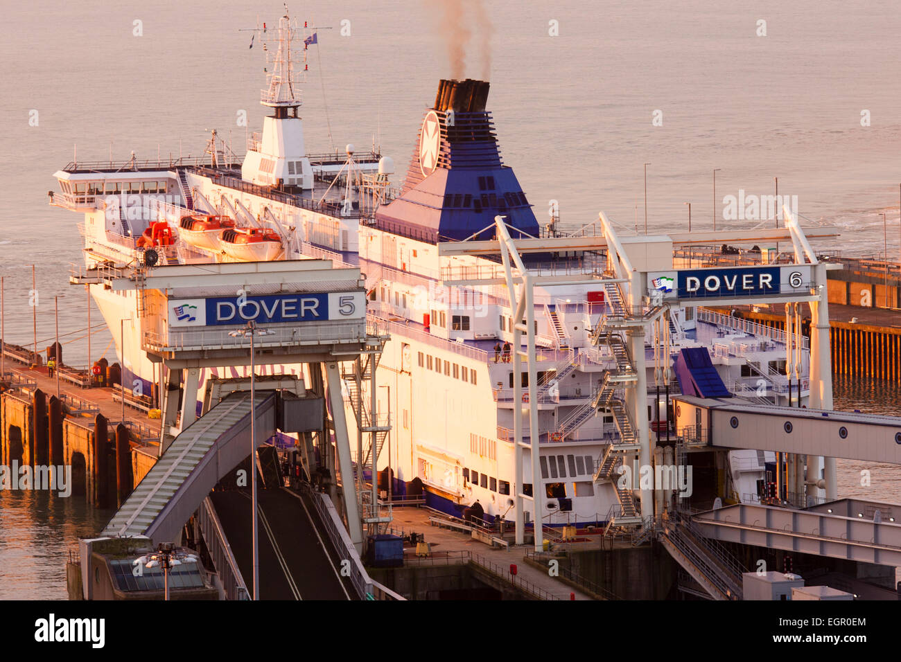 England, Dover. English Channel. Dawn. Car ferry docked stern first, loaded and ready to depart, ship lit up by - Stock Image