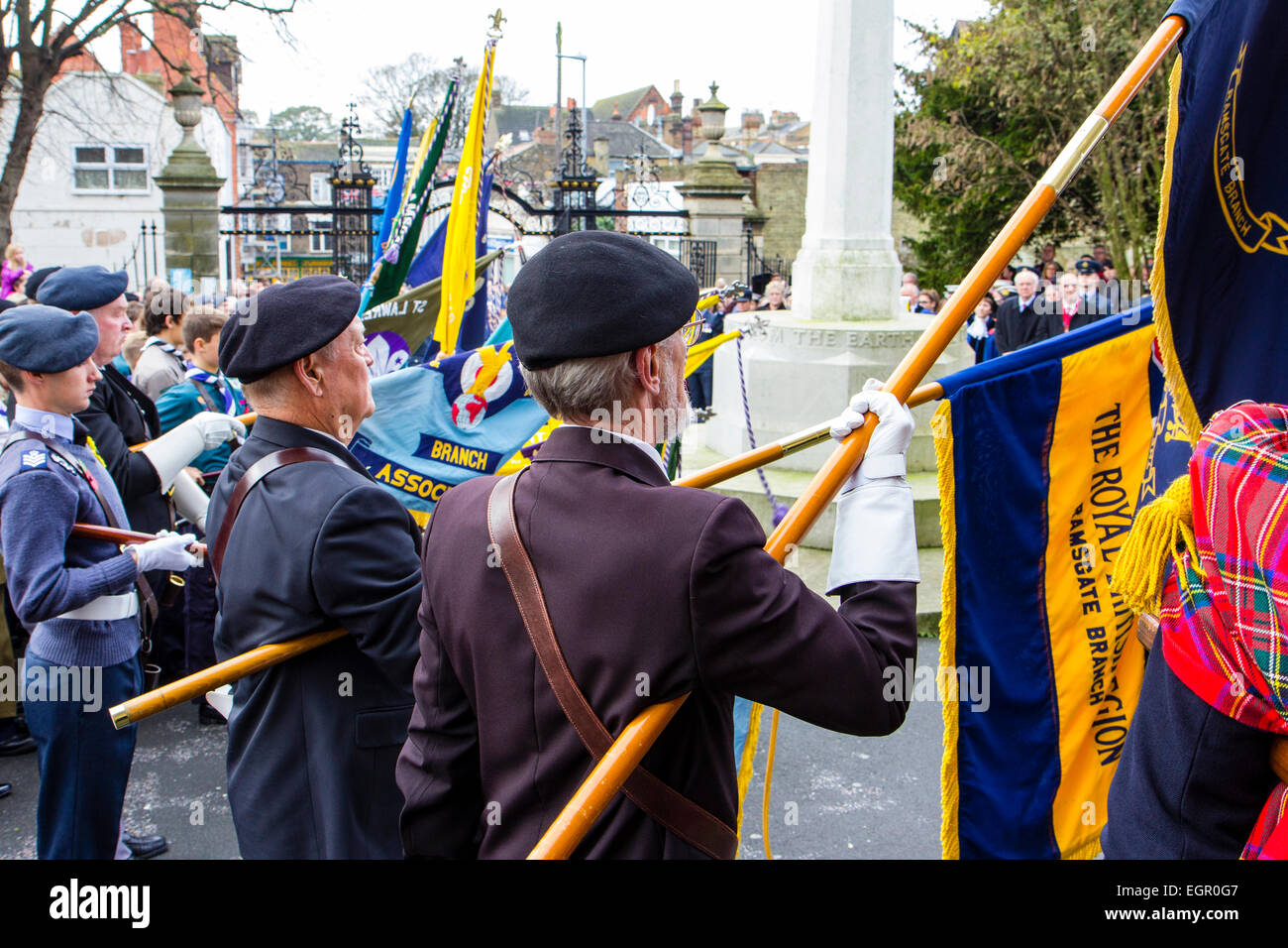 Ramsgate, remembrance sunday. Row of senior ex-servicemen standing to attention while lowering banners and flags - Stock Image