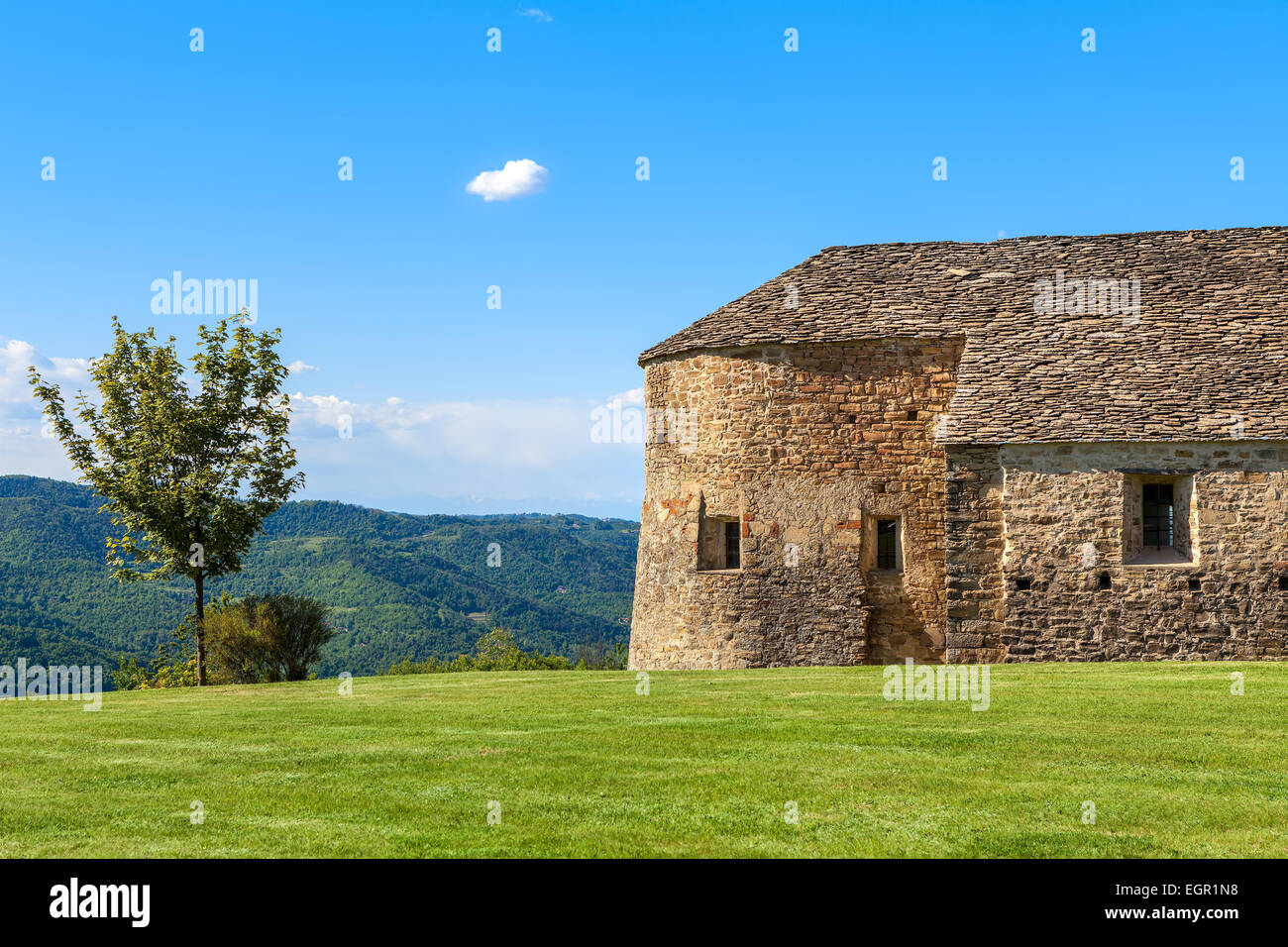 Lone tree and old stone church on green lawn under blue sky in Piedmont, Northern Italy. - Stock Image