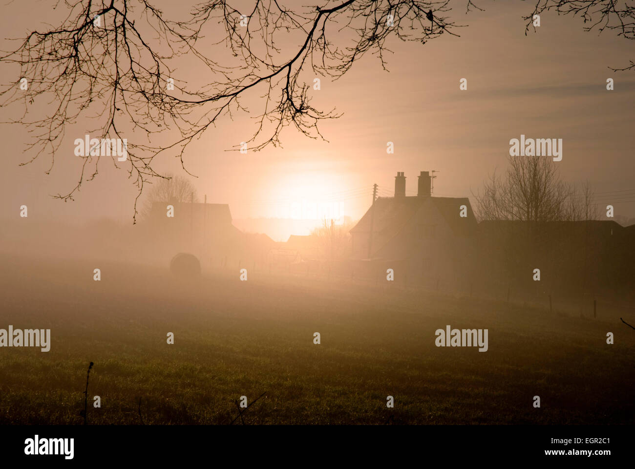 Dawn - rising sun shrouded by mist - farm buildings in dark silhouette against an orange tinted sky - promise of - Stock Image