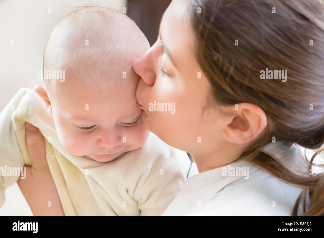 A young mother kissing her little baby - Stock Image