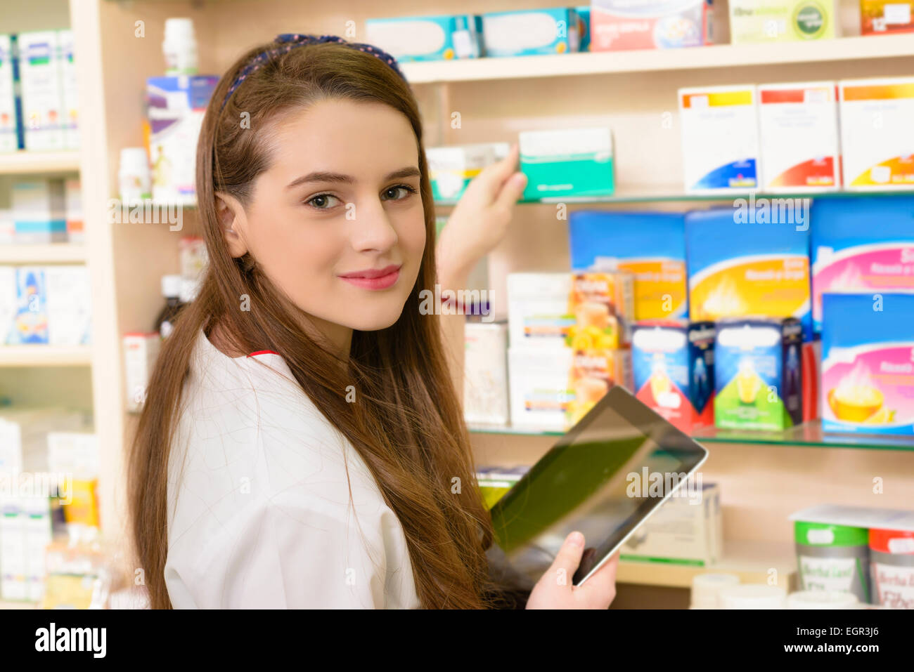 Young female pharmacist in a drugstore working on a tablet pc - Stock Image