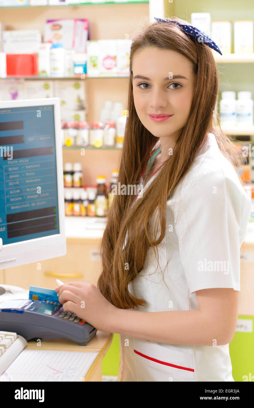 Young female pharmacist holding a credit card Stock Photo