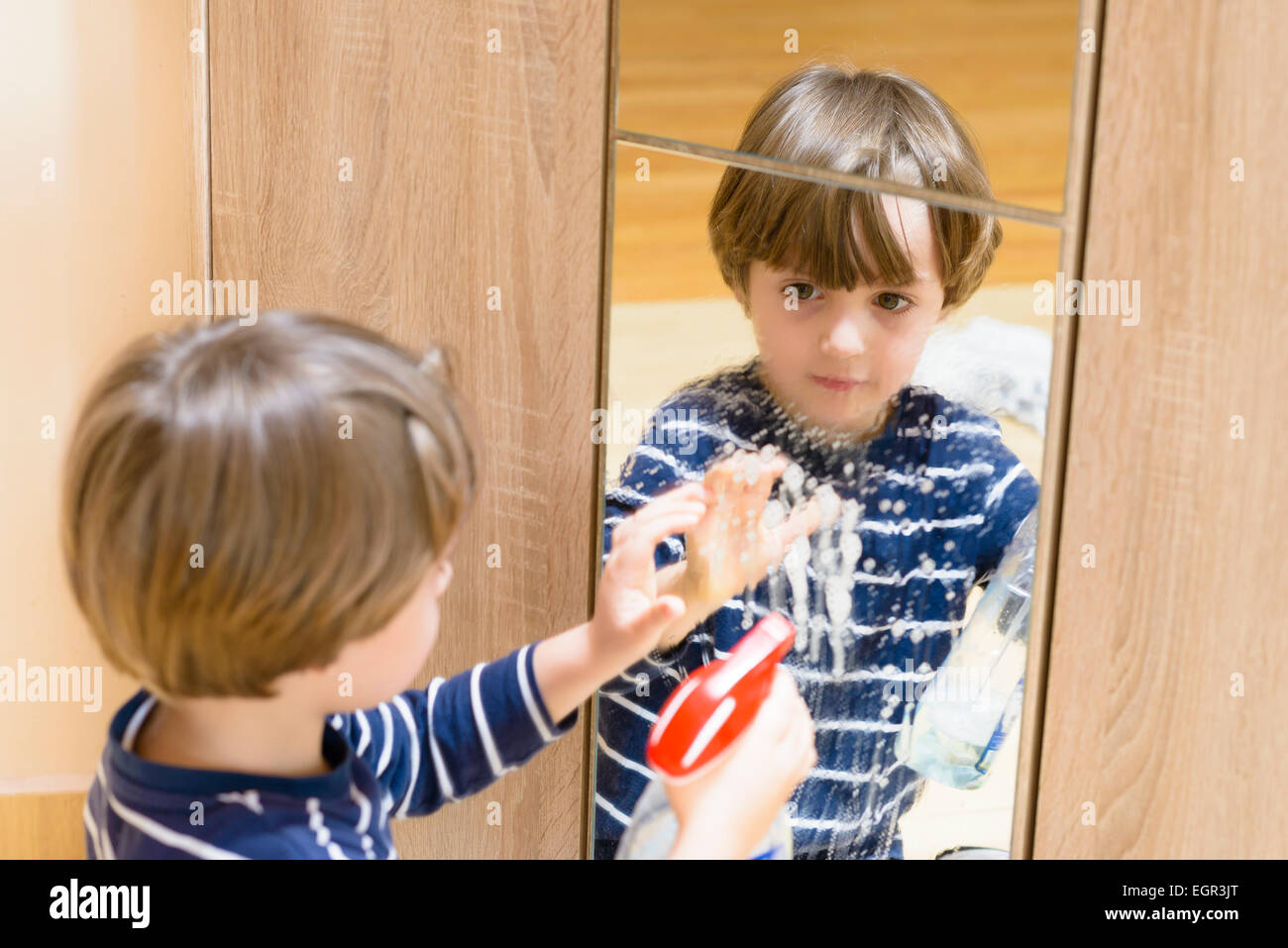 Cute boy cleaning the mirror using some spray - Stock Image