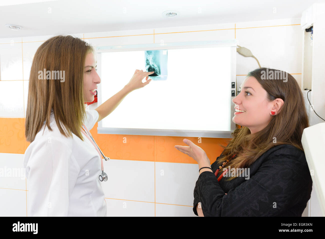 Patient looking with doctor at x-ray image in a hospital - Stock Image