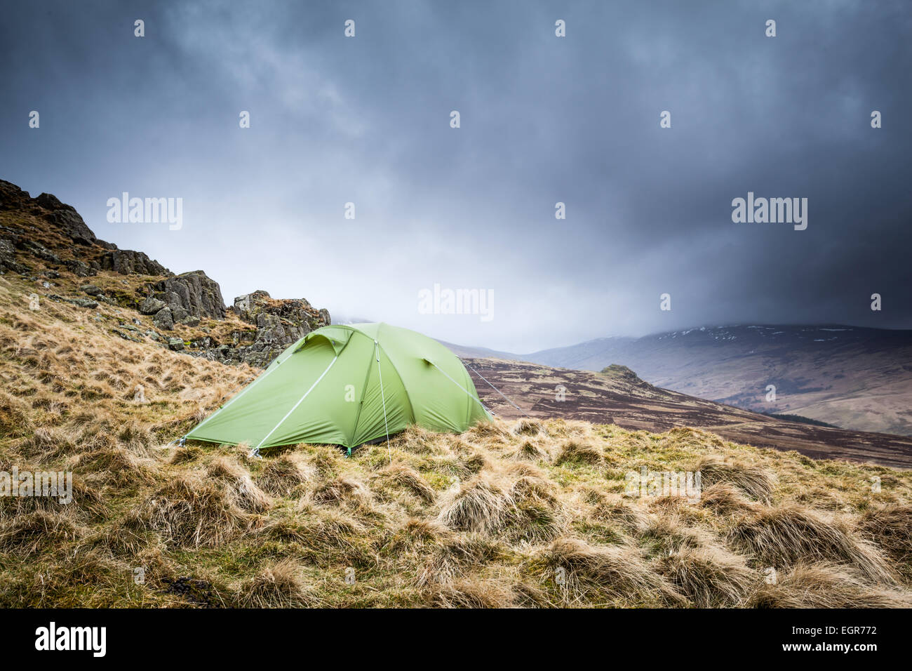 Wild Camping at the end of Winter at Langlee Crags overlooking Cheviot hill in the wild Northumberland countryside - Stock Image