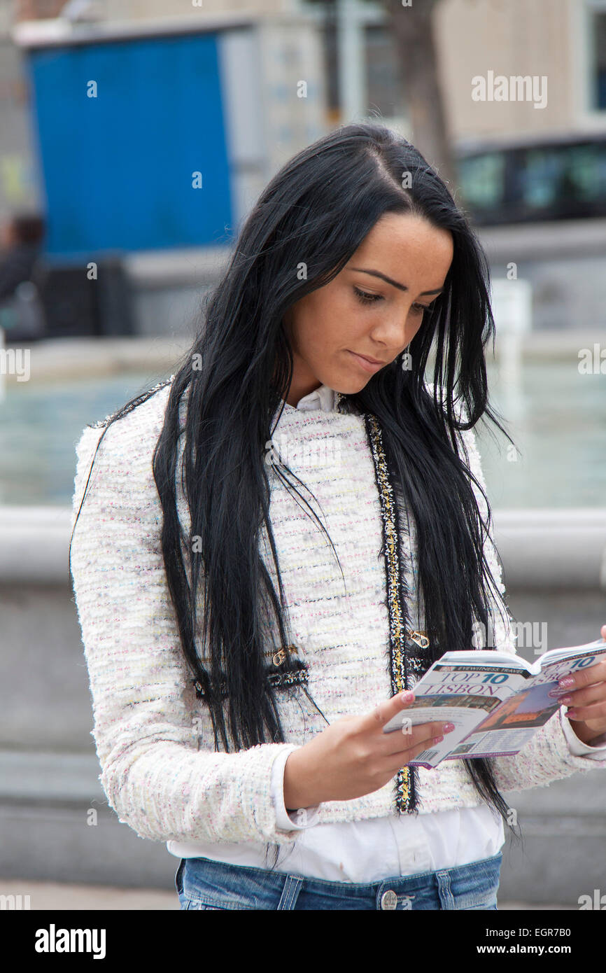 A young woman on vacation and reading a travel guide - Stock Image
