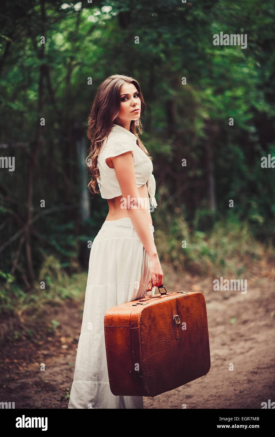 Beautiful young sad woman with suitcase in hand standing on a road - Stock Image
