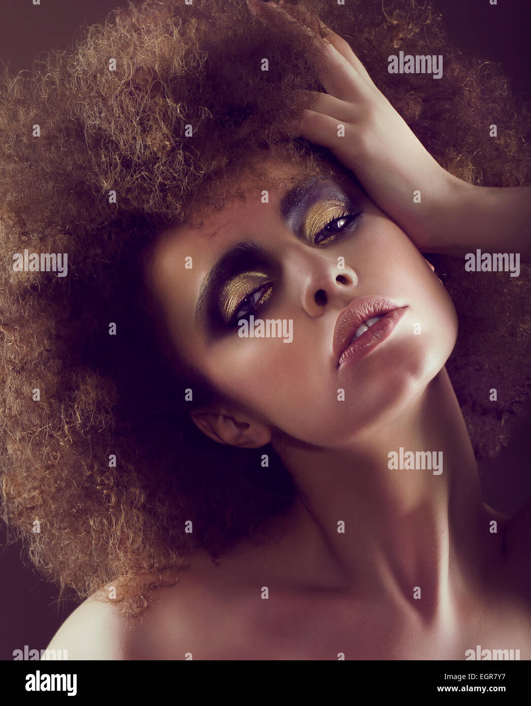 Dreamy Woman with Frizzy Hairstyle and Golden Eyeshadow - Stock Image