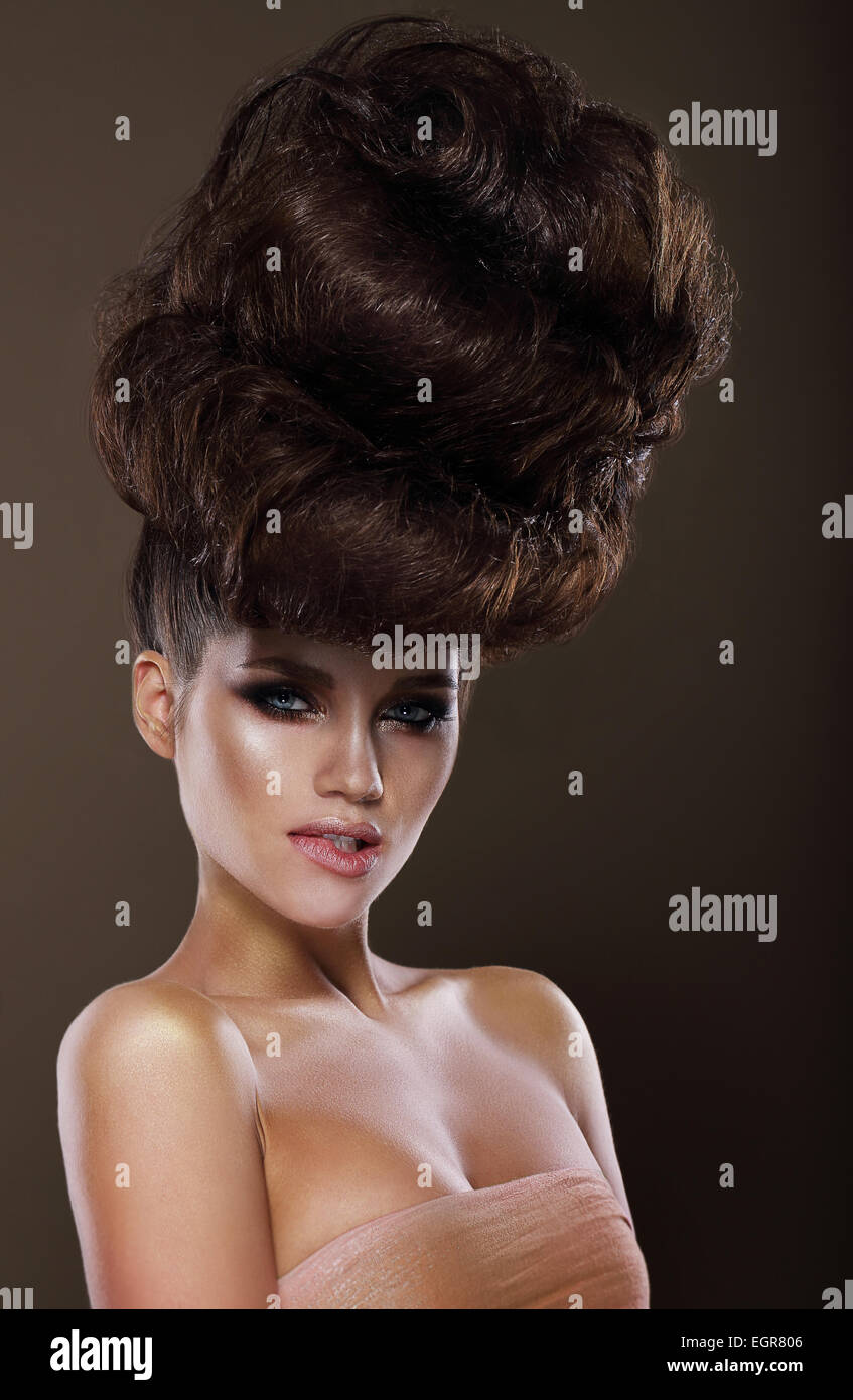 Updo. Trendy Woman with Creative Hairstyle - Stock Image