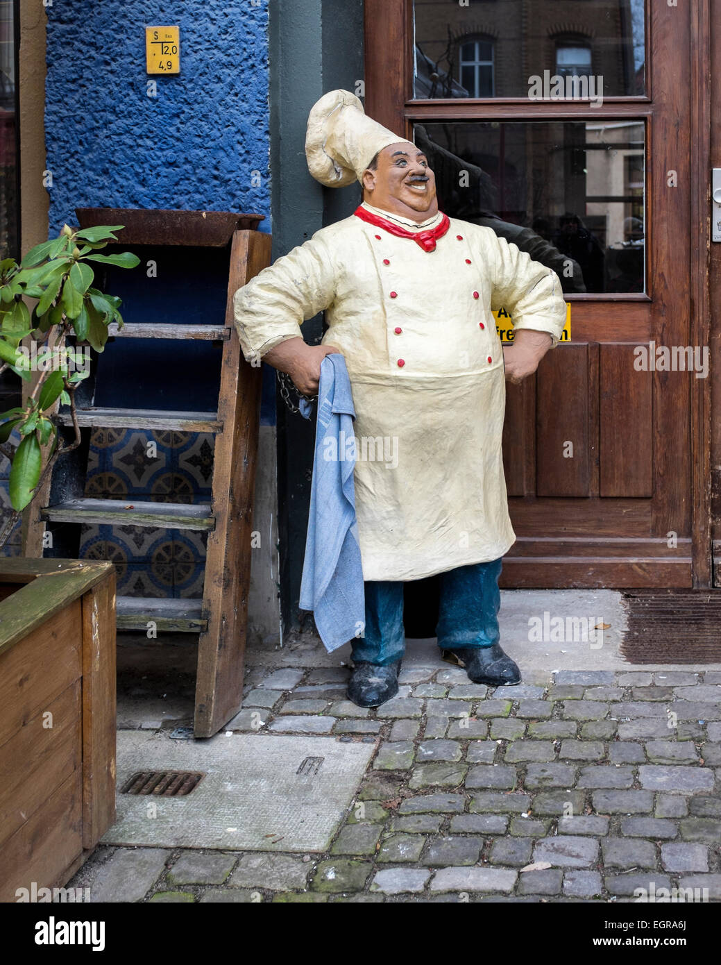 Berlin Restaurant mascot, life-size smiling chef holding dishcloth at entrance, Mitte, Berlin - Stock Image
