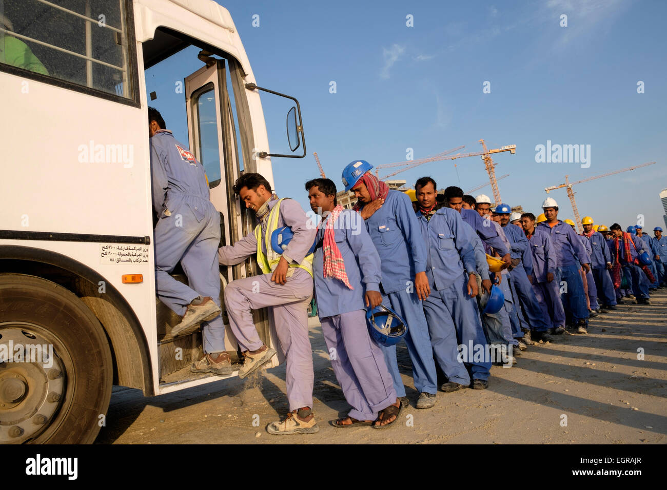 Construction workers queuing to get on bus to living quarters at end of working day in Dubai United Arab Emirates - Stock Image