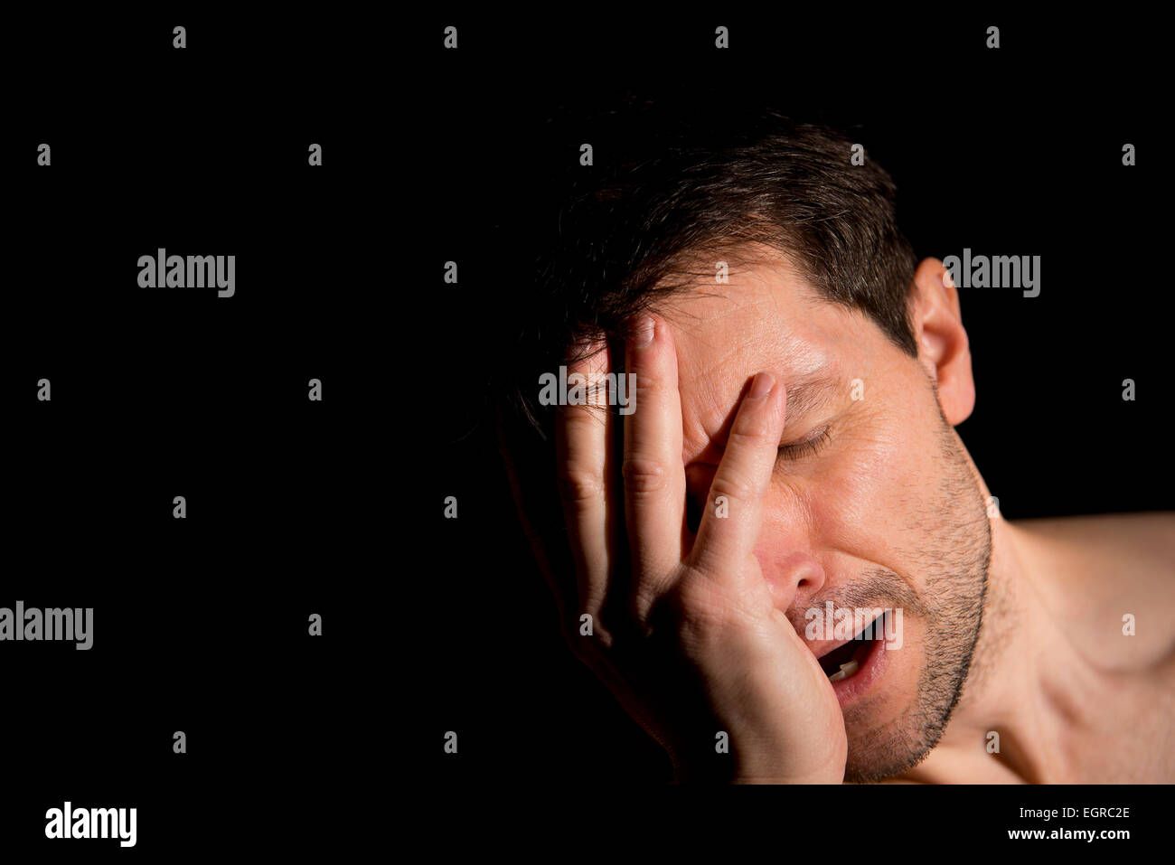Man suffering with depression, has his head in his hands. The background is black and dark shadows cast over the - Stock Image