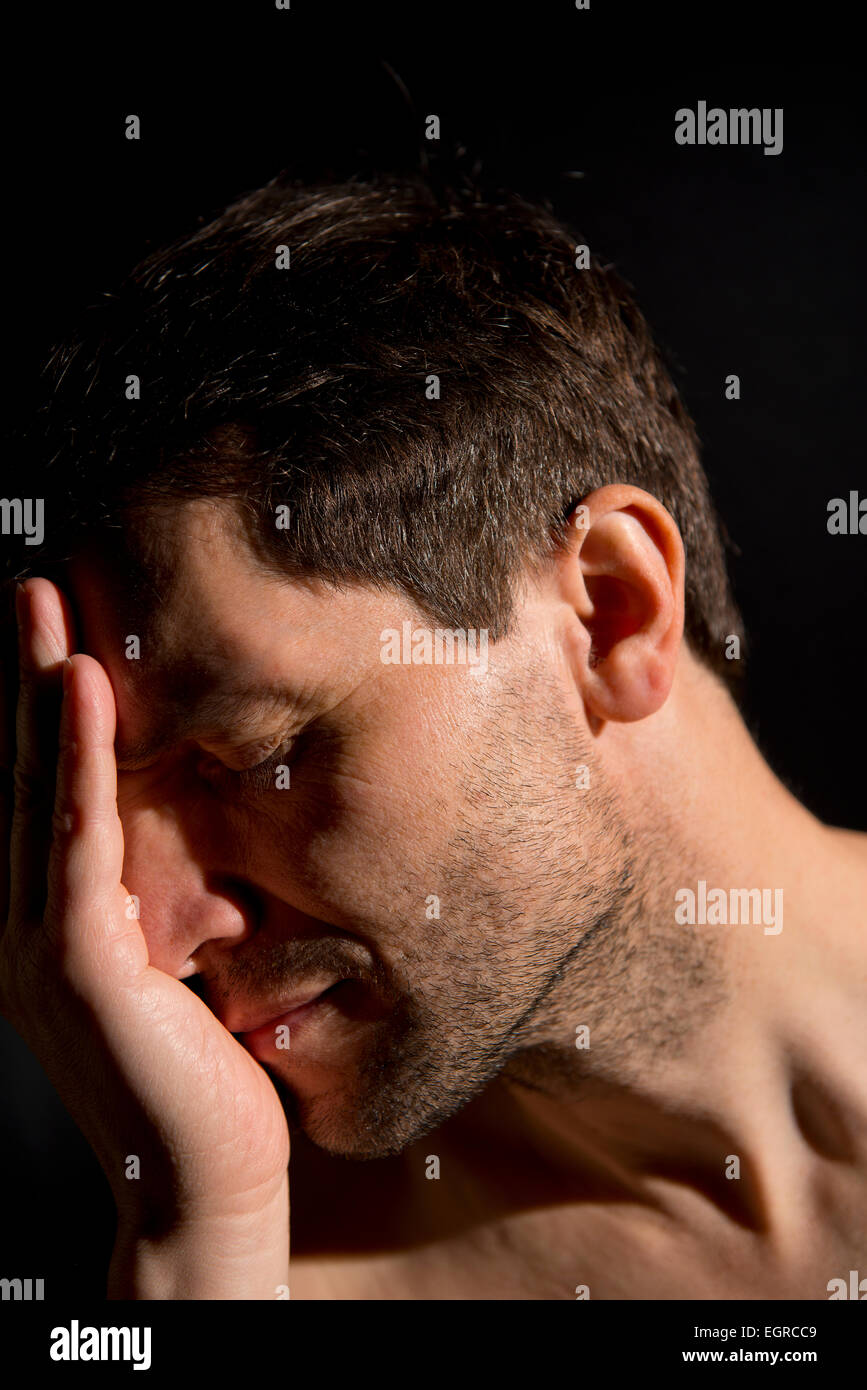 Man suffering with depression, has his head in his hands. The background is black and dark shadows cast over the Stock Photo