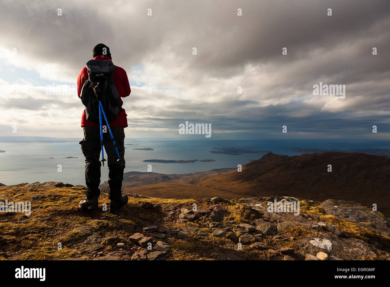 Hillwalker overlooking the sea from a hill in Coigach in the far north of Scotland - Stock Image