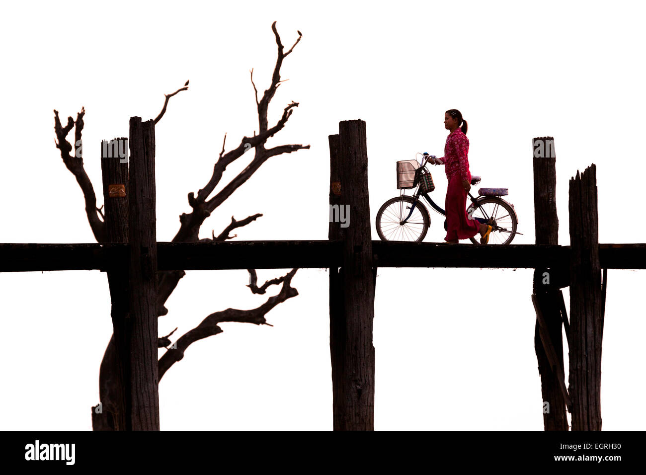 A woman pushing a bicycle on U Bein bridge, Mandalay, Myanmar ( Burma ), Asia Stock Photo