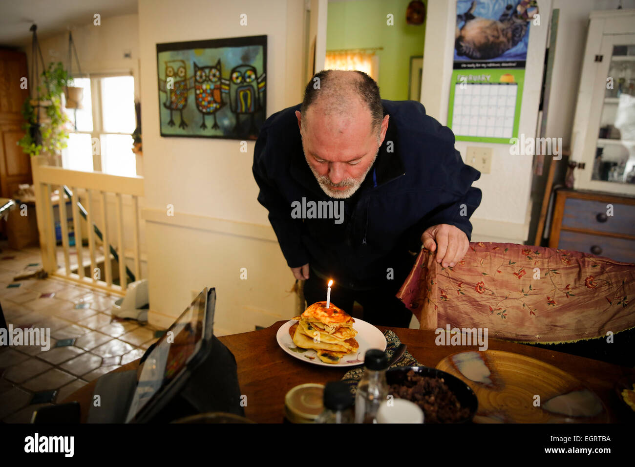 Man in his 50s blowing out candles on birthday pancakes on his birthday - Stock Image