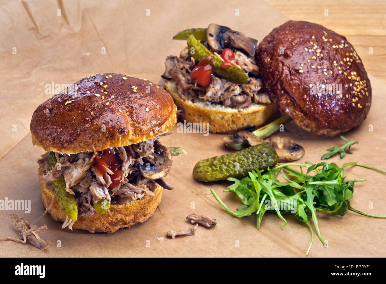 Two sandwiches with pulled pork, pickles and grilled mushrooms  in home made brioche buns. - Stock Image