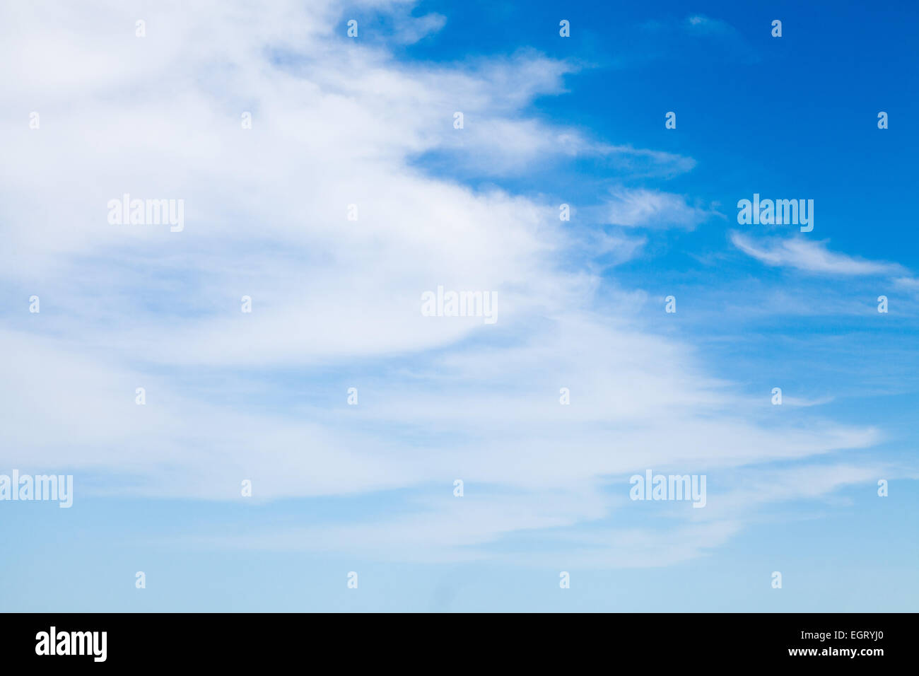 white puffy wispy clouds make a beautiful cloudscape decorating the blue sky and foretelling of the weather. - Stock Image