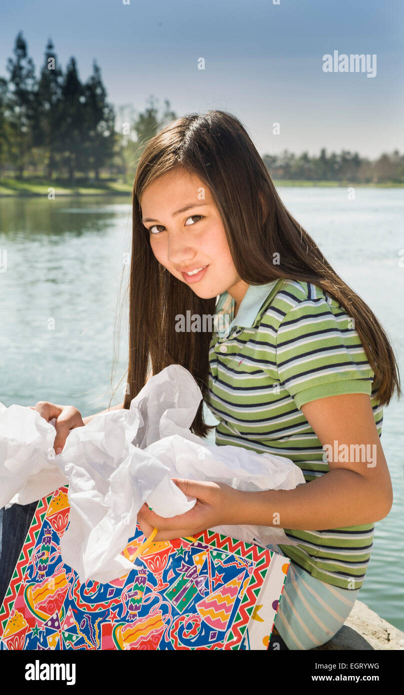 11 12 13 Year Old Young Person People Tween Tweens Vietnamese Caucasian Girl Opening Birthday Presents Gifts Outside Smiling At Camera MR C Myrleen Pearson