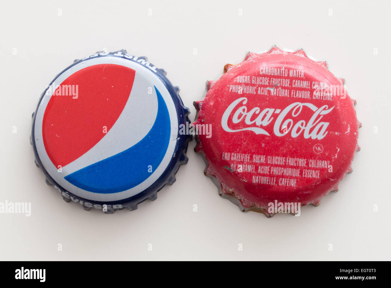 A Pepsi bottle cap and a Coca-Cola bottle cap. - Stock Image