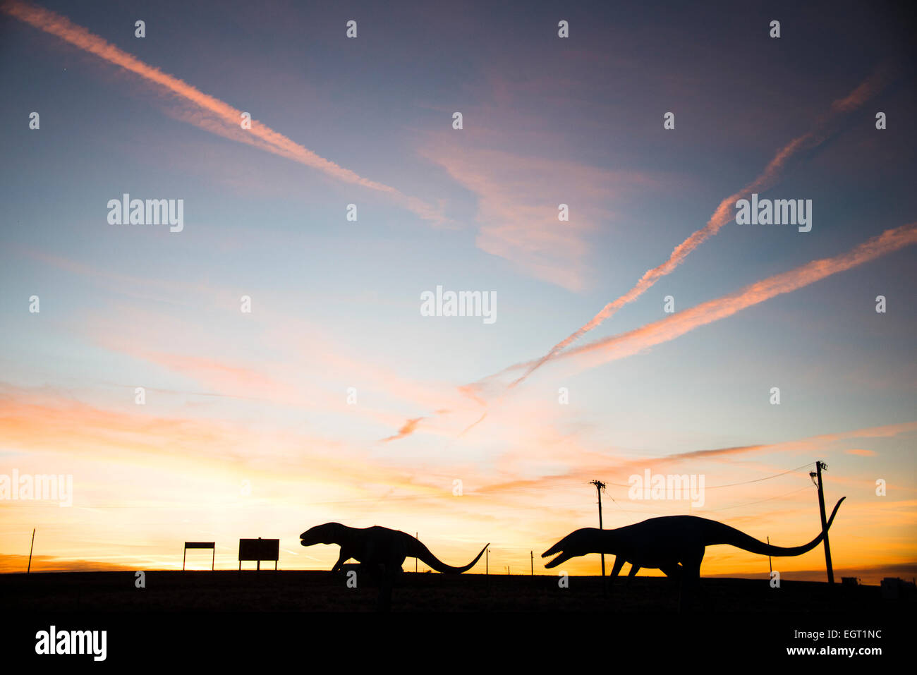 Giant raptor dinosaur figures silhouetted against sunset near Holbrook on Route 66 Arizona, USA - Stock Image