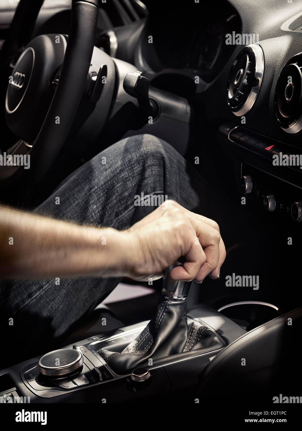 Closeup of a man driving a car with his hand on a gear shift lever - Stock Image