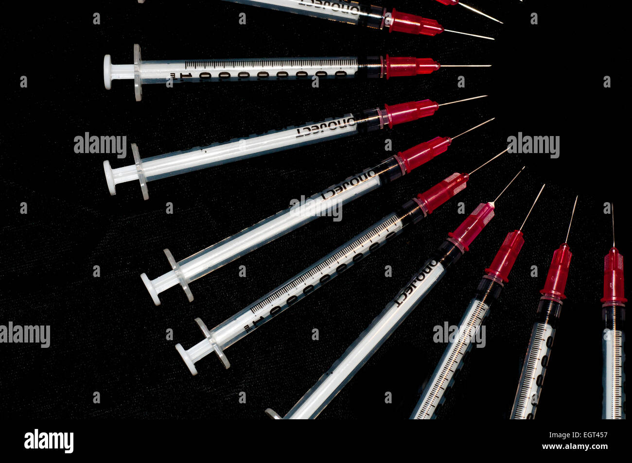 Used syringes arranged in an arc; concept shot for drug abuse - Stock Image