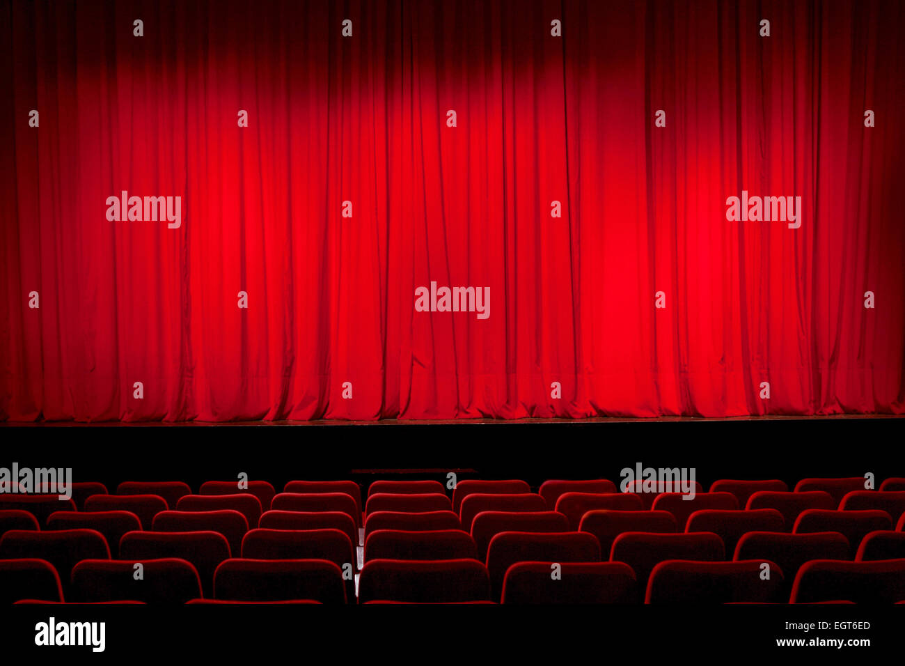 Closed red curtain in an empty theatre - Stock Image