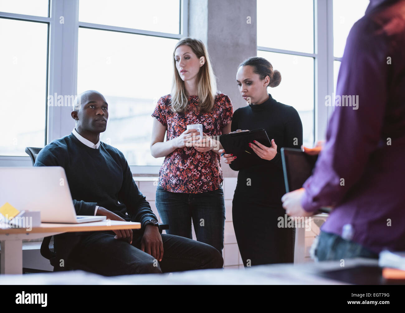 Business people having informal meeting in office. Diverse team of young people discussing work. - Stock Image