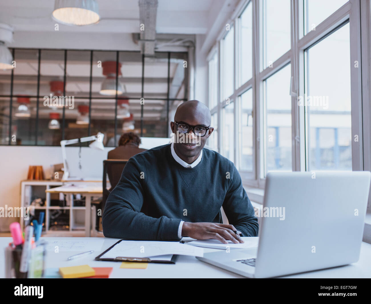 Portrait of confident young man sitting at his desk with laptop. African businessman working in modern office. - Stock Image
