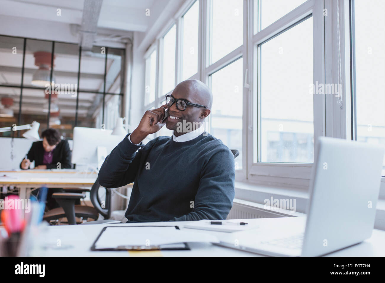 Young man talking on his mobile phone in office. African executive sitting at his desk with laptop - Stock Image