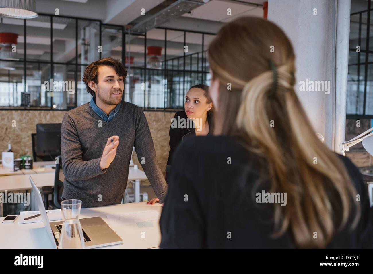Young man explaining new business plan to coworkers during a meeting around a table in office. - Stock Image