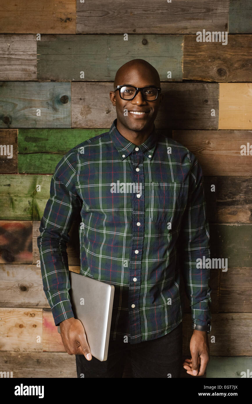 Portrait of young african student with laptop smiling at camera. Bald young man wearing glasses standing against - Stock Image
