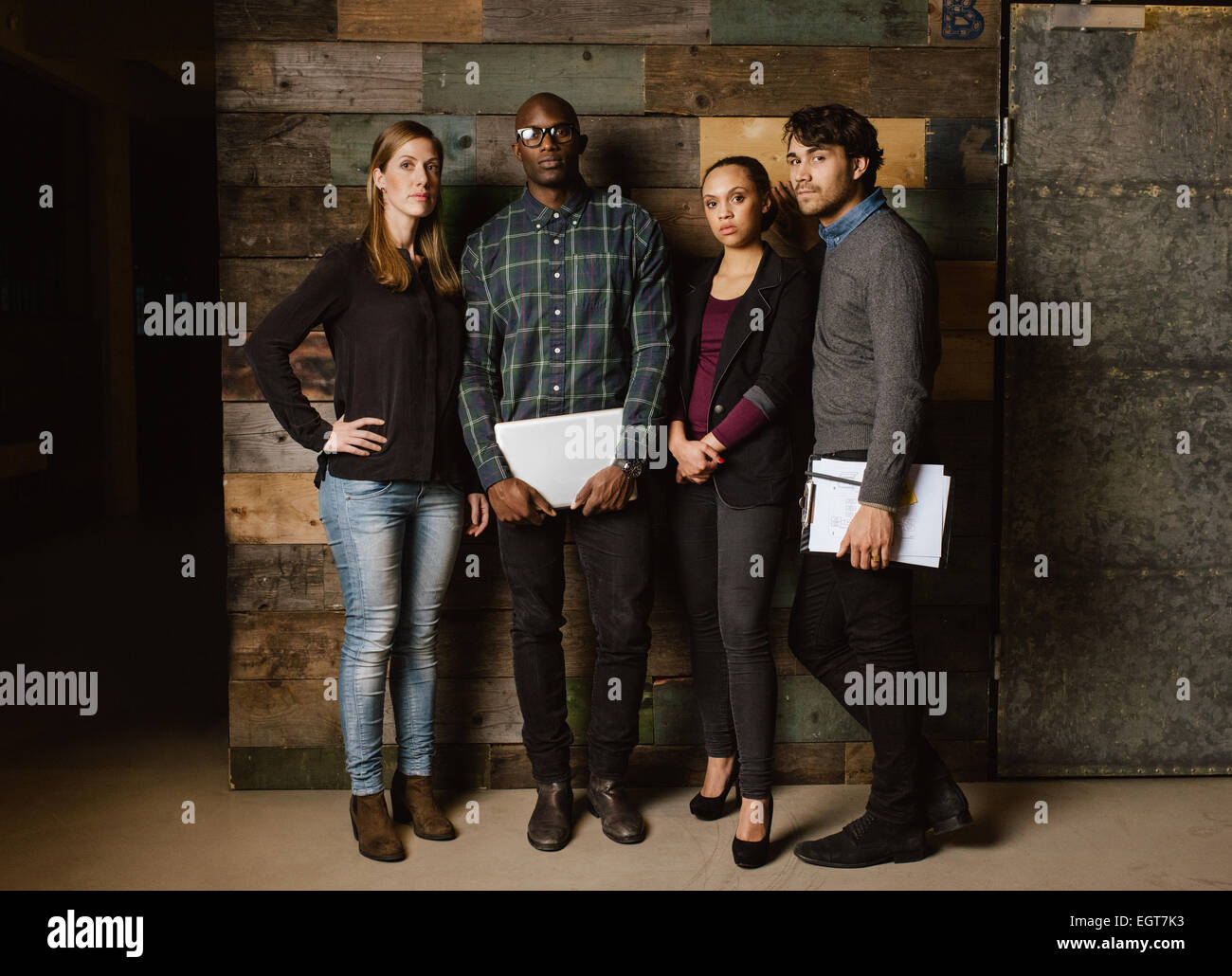 Portrait of young professionals standing together in office. Diverse group of young executives at work. - Stock Image