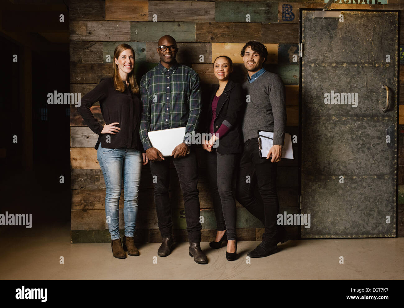 Full length portrait of successful business team standing in an office. Multiracial business professional posing - Stock Image