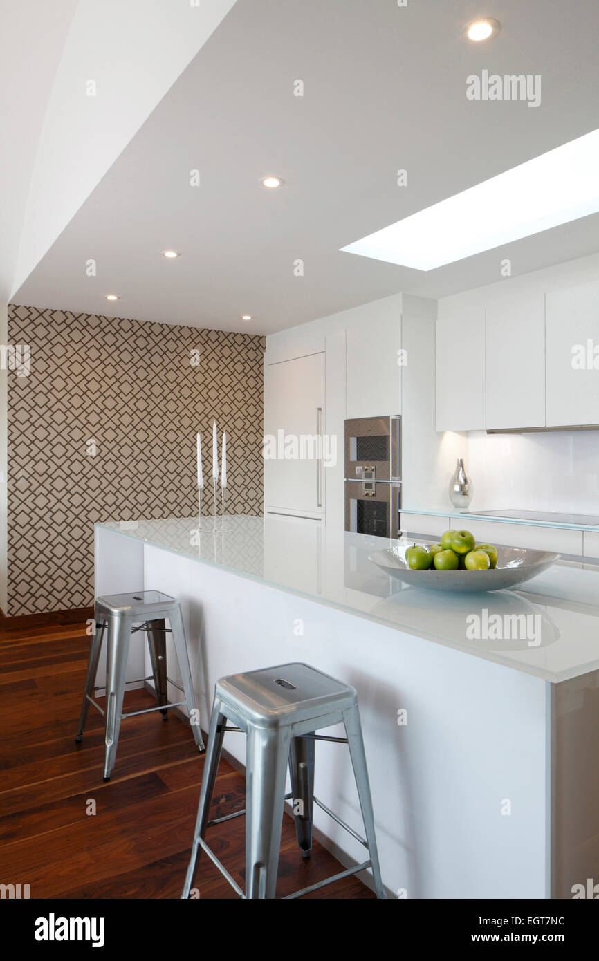 White Kitchen Beneath Skylight With Patterned Wallpaper Feature Wall
