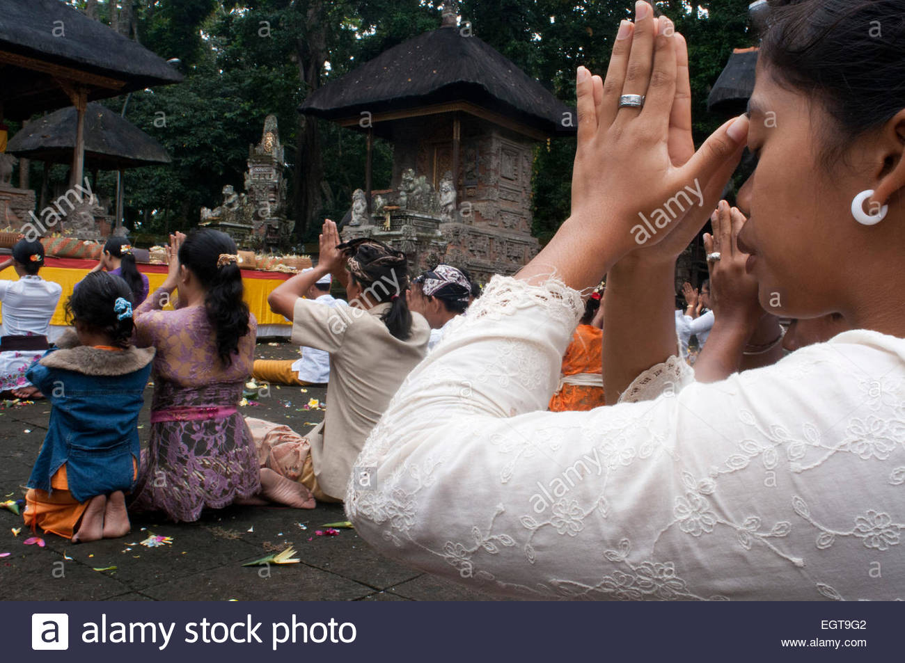 A BALINESE family and friends prays at PURA TIRTA EMPUL a Hindu Temple complex and cold springs - TAMPAKSIRING, - Stock Image