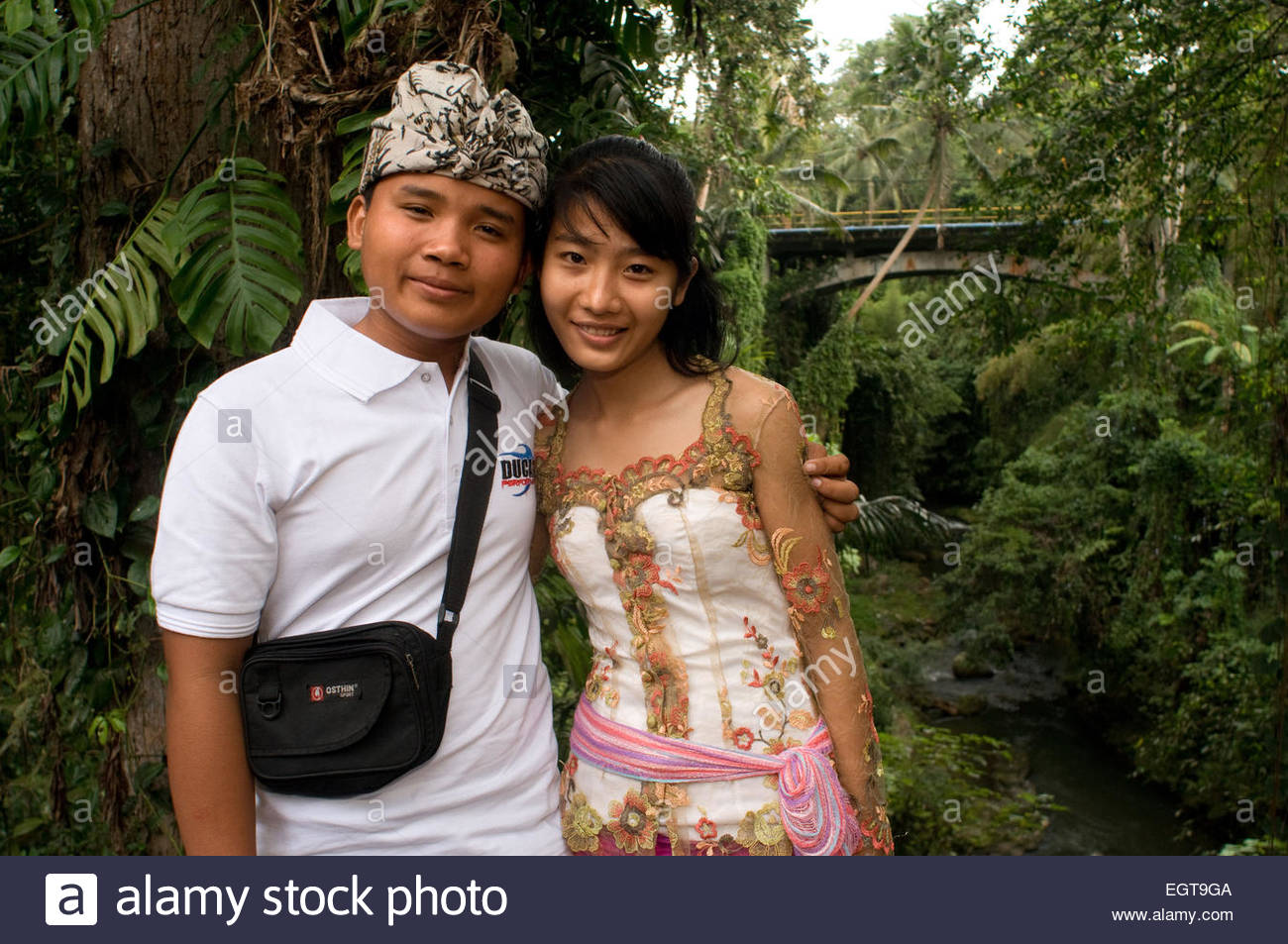 A couple in front of the temple Pura Gunung Lebah, Ubud, Bali, Gunung Lebah was constructed in the 8th century by - Stock Image