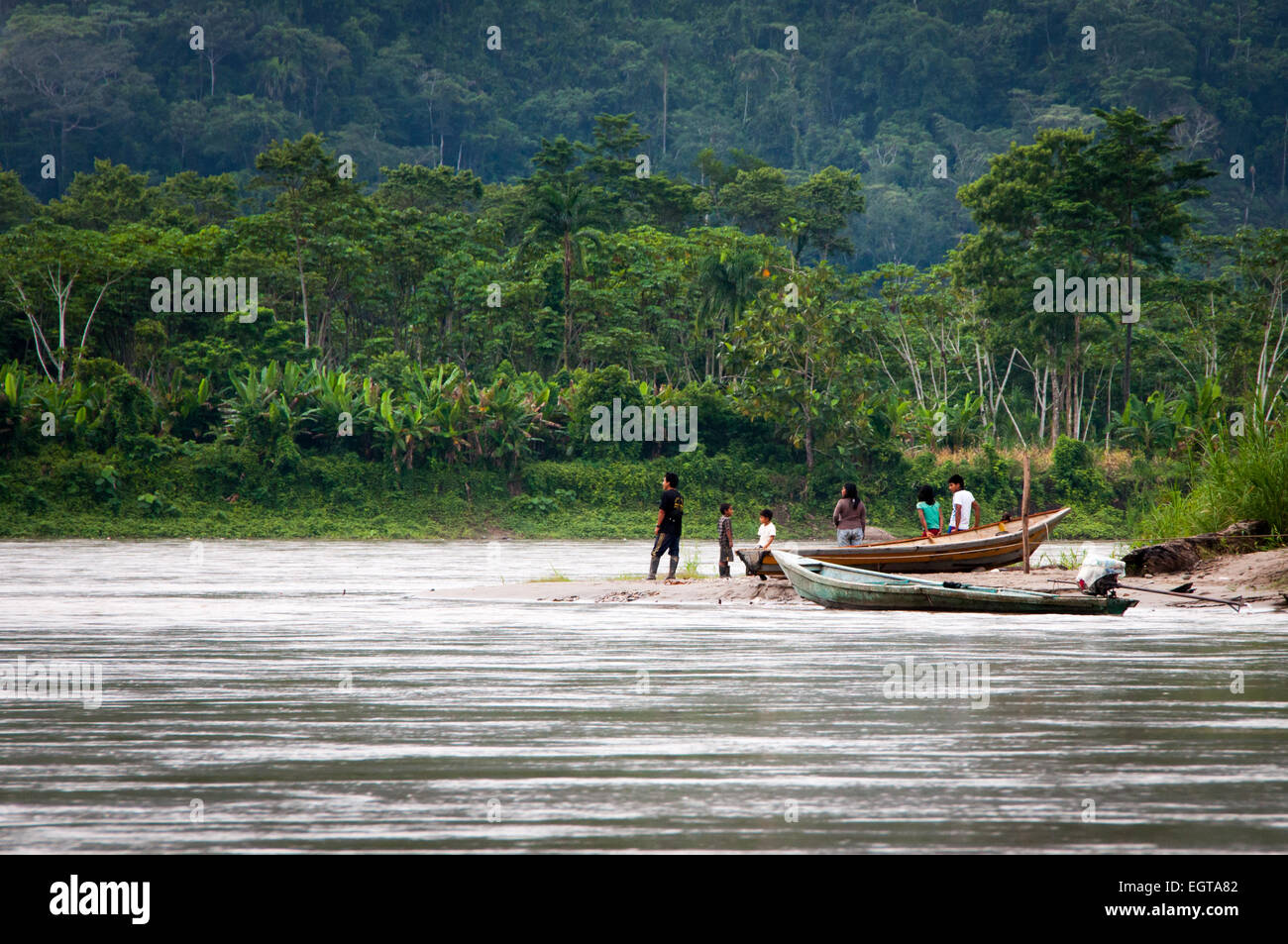 Local men, women and children with boats on the sandy bank of Amazon region river of northern Peru - Stock Image
