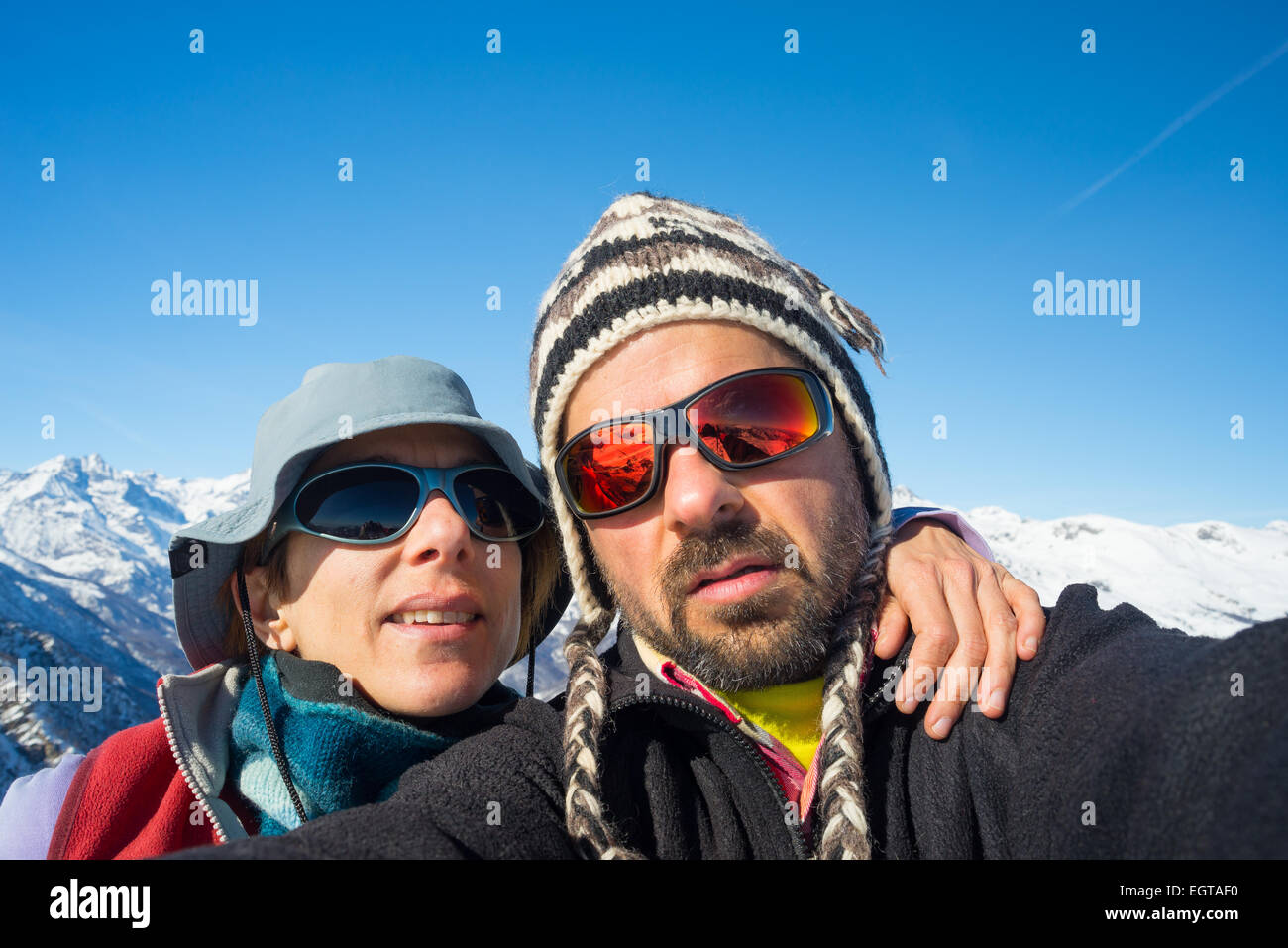 Adult european couple taking selfie in the beautiful natural landscape of  the italian Alps in late winter season.