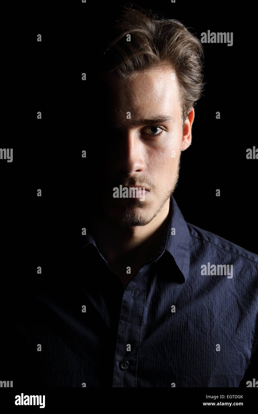 Portrait of an angry man expression isolated on a black background - Stock Image