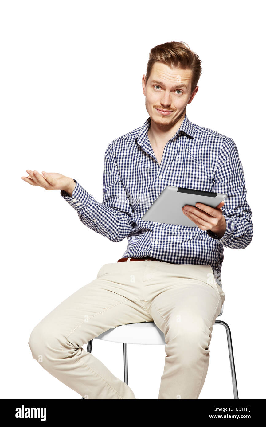 Disappointed young man holding tablet. Studio shot isolated on white. - Stock Image