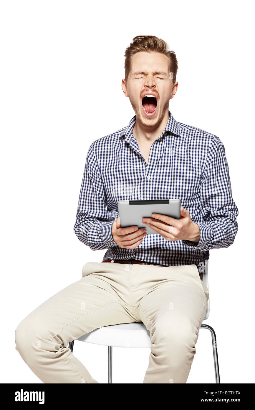 Studio shot of young yawning man. Facial expression. - Stock Image