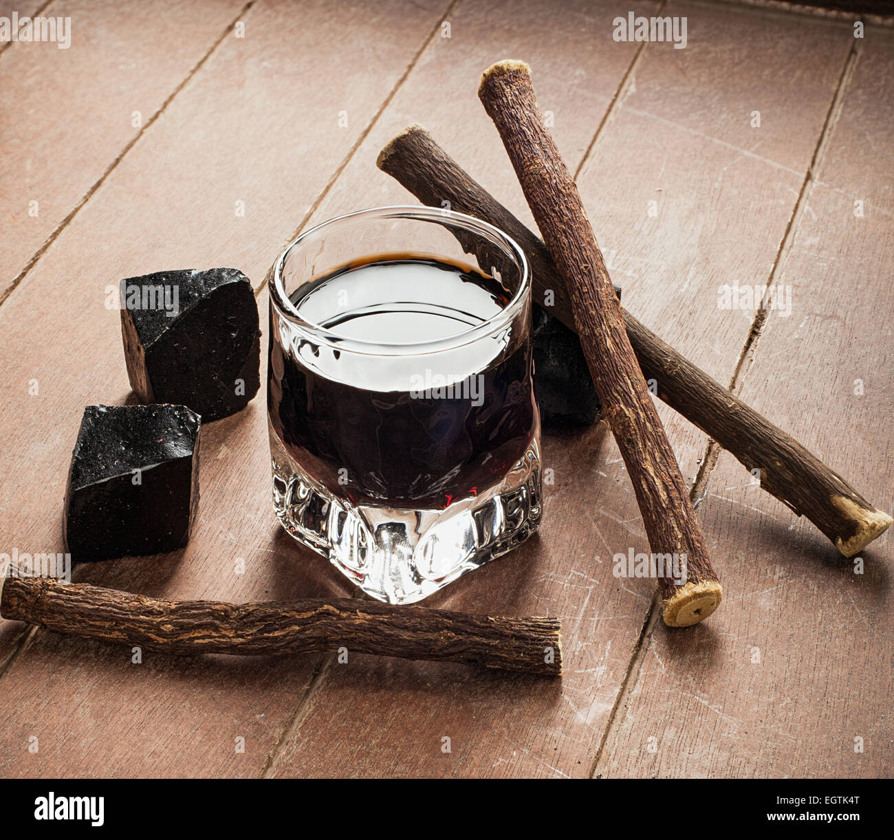 Licorice liqueur with pure blocks and roots on wooden table. - Stock Image