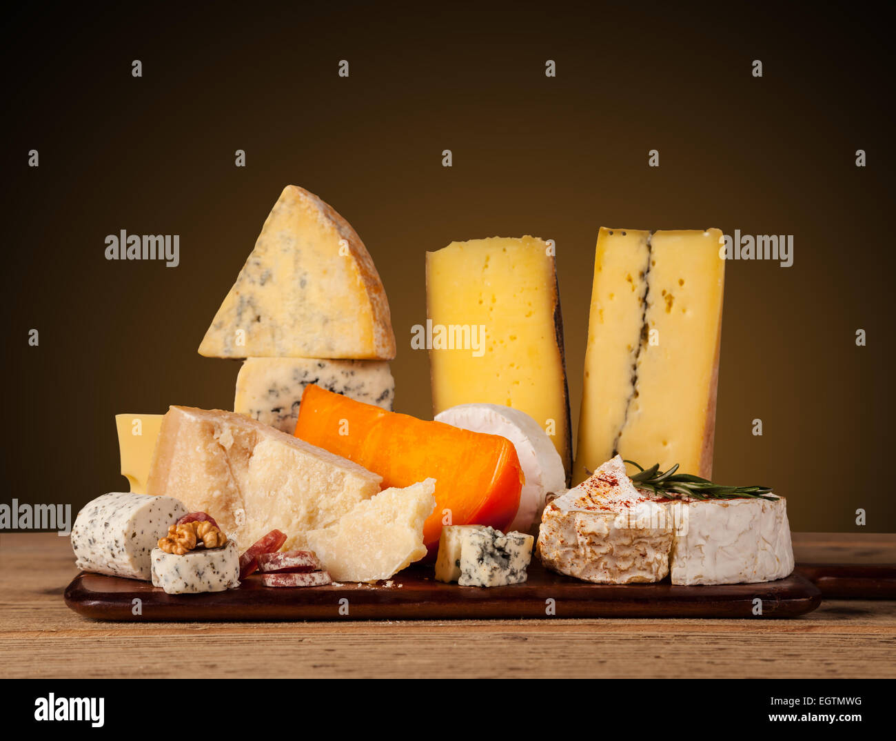 Various kind of cheese served on wooden table - Stock Image