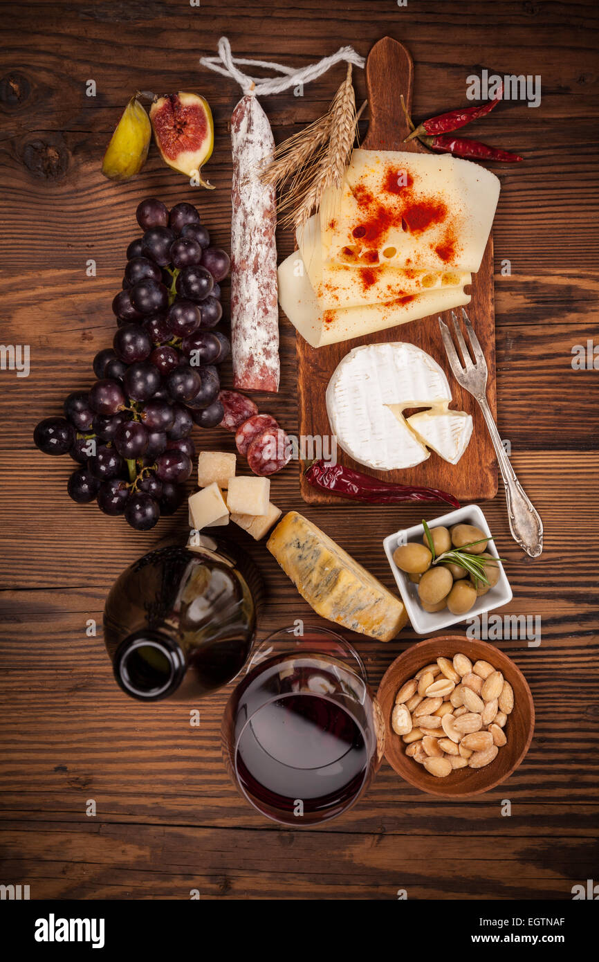 Cheese arrangement served on cutting board. Shot from aerial view - Stock Image