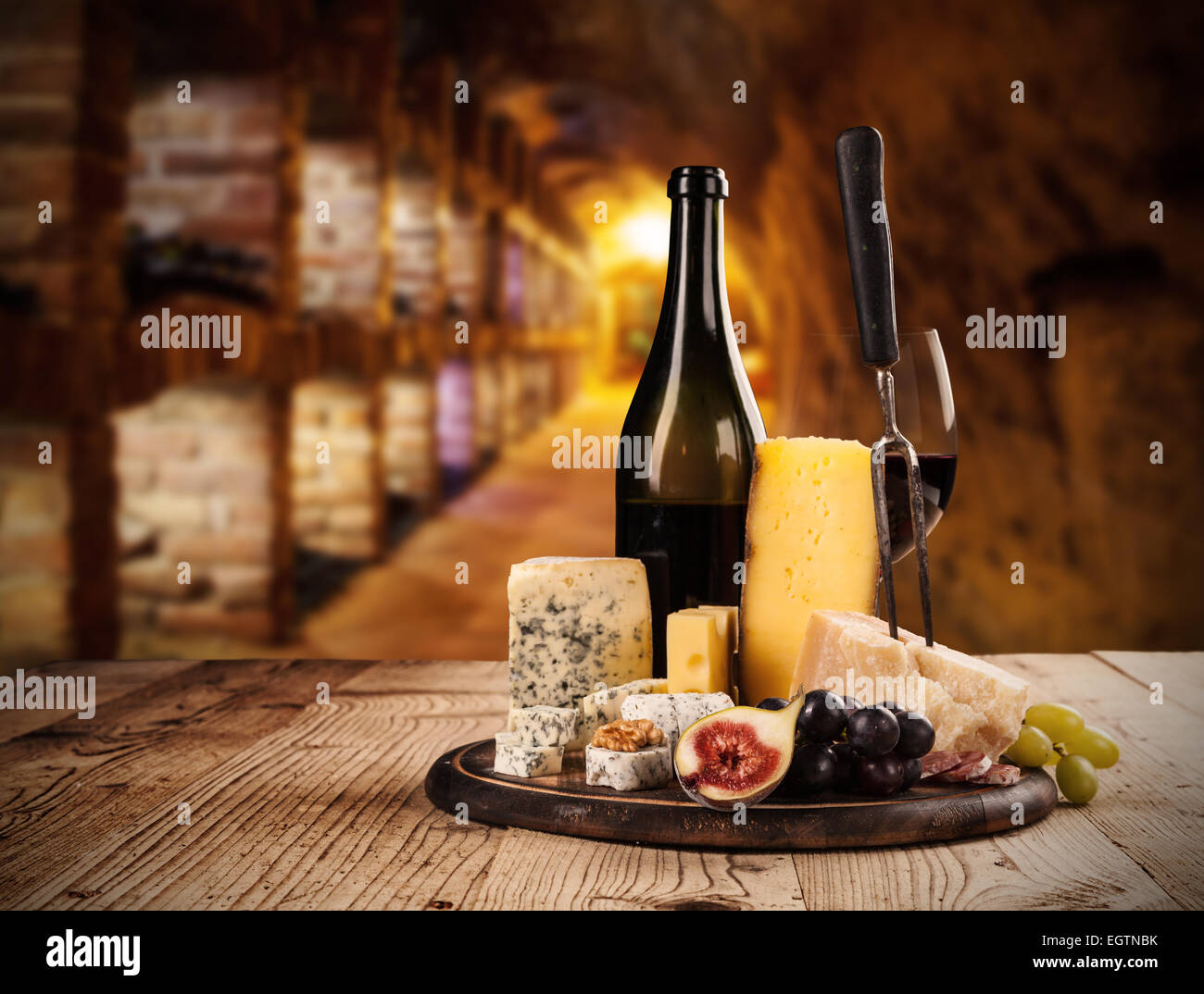 Various kind of cheese with red wine in cellar - Stock Image